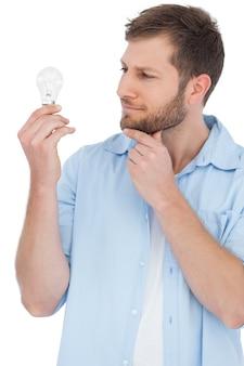 Modello scettico che tiene una lampadina e che tocca il suo mento
