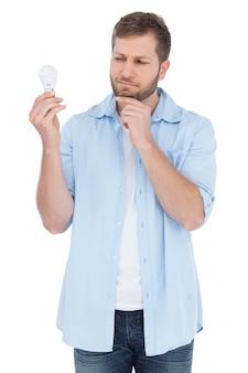 Modello scettico che tiene una lampadina