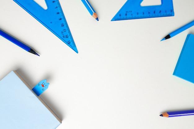 Accessori per la scuola sullo spazio della copia di vista superiore del fondo blu e bianco