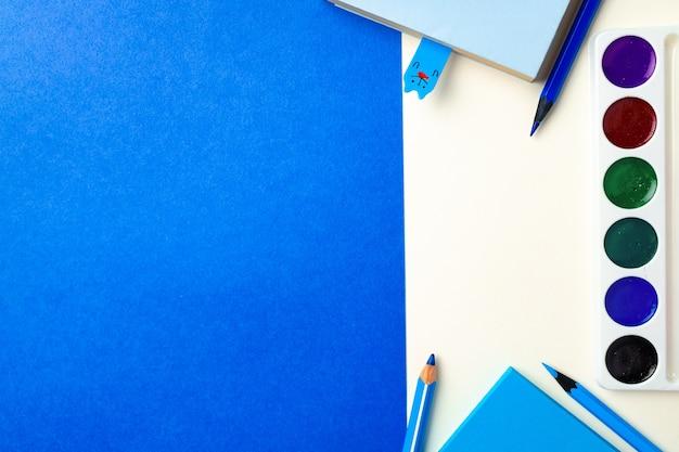 Accessori per la scuola su sfondo blu e bianco vista dall'alto lo spazio della copia