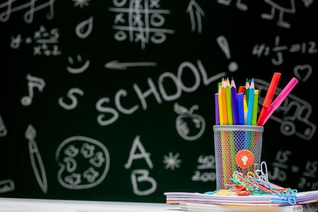 Accessori per la scuola. libri, globo, matite e vari articoli per ufficio che si trovano sulla scrivania