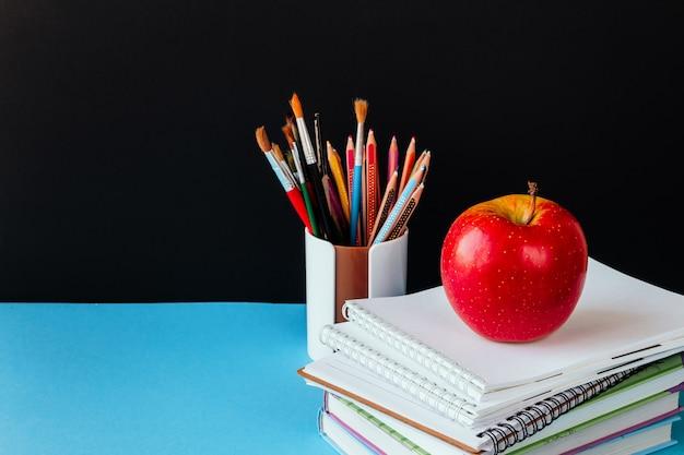 Accessori per la scuola, blocco note, matite, pennarelli, mela.