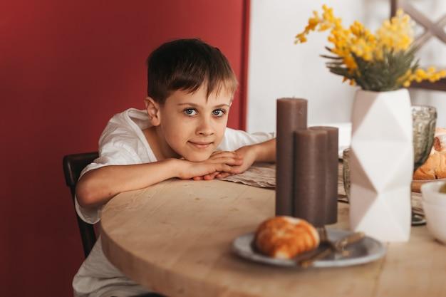 Un ragazzo in età scolare siede al tavolo della cucina. aspettando il pranzo