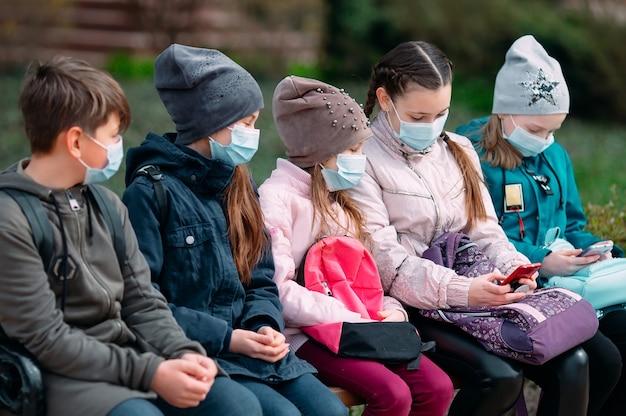 I bambini in età scolare con maschere mediche si siedono sulla panchina.