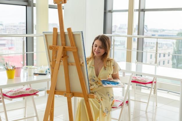 Scuola d'arte, liceo artistico, educazione per gruppi di giovani studenti. felice giovane donna sorridente, ragazza che impara a dipingere.