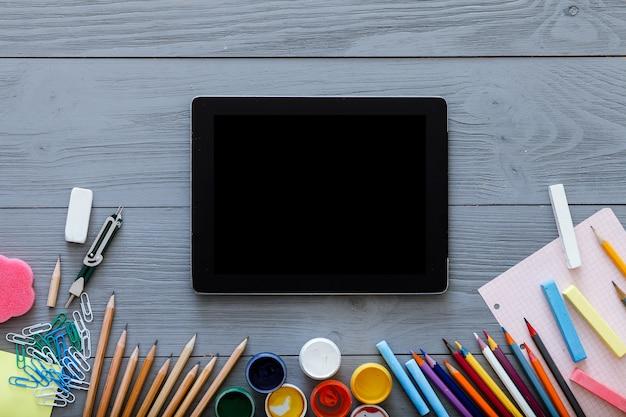 Sfondo di scuola, forniture per studio per bambini e schermo digitale per tablet su fondo di legno grigio grigio, nuove applicazioni online di tecnologie web didattiche per l'apprendimento del disegno, vista dall'alto