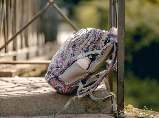 Zaino della scuola sdraiato per strada. zainetto casual per alunna bambina della classe primaria