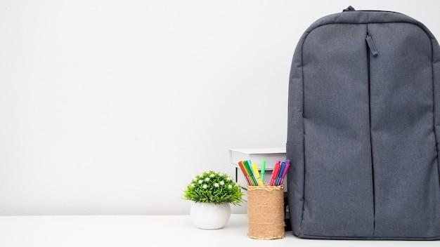 Zaino scuola con astuccio e libri sulla scrivania sfondo bianco copia spazio