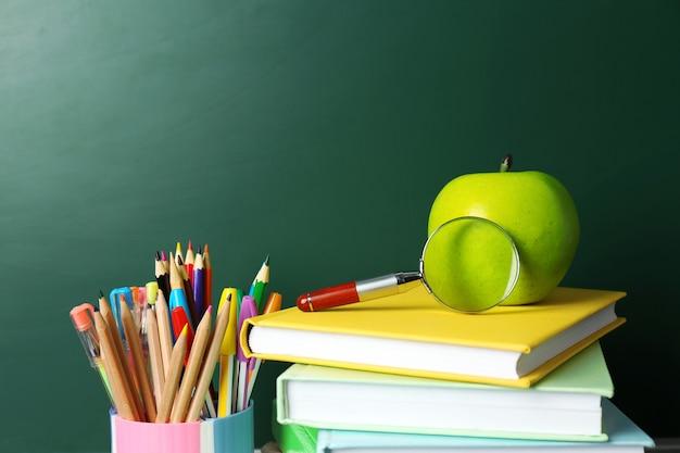 Libri scolastici sulla scrivania vicino alla lavagna