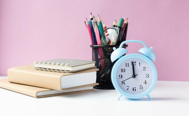 Libri scolastici con sveglia sullo sfondo del consiglio scolastico verde