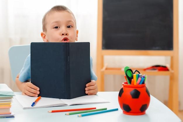 Il ragazzo di scuola che si siede a casa lo scrittorio di menzogne dell'aula ha riempito di materiale di addestramento dei libri lo scolaro che dorme annoiato pigro