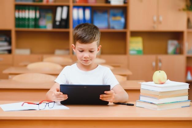 Scolaro che utilizza il computer tablet in classe