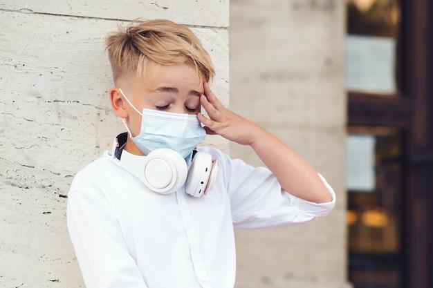 Scolaro che indossa una maschera per la protezione dal coronavirus. torna al concetto di scuola. istruzione durante la pandemia. ragazzo stanco in maschera di sicurezza dopo le lezioni. coronavirus e vita scolastica.