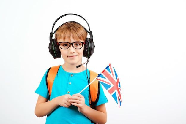 Ragazzo della scuola con le cuffie che tengono la bandiera britannica. scuola di lingua inglese online. lezioni e apprendimento delle lingue straniere.