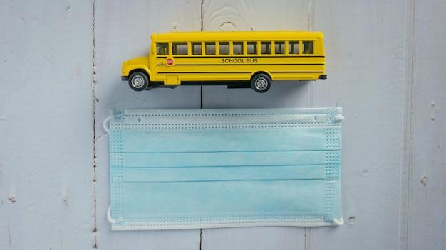 Lo scuolabus e la maschera sul tavolo di legno per l'istruzione o il concetto medico
