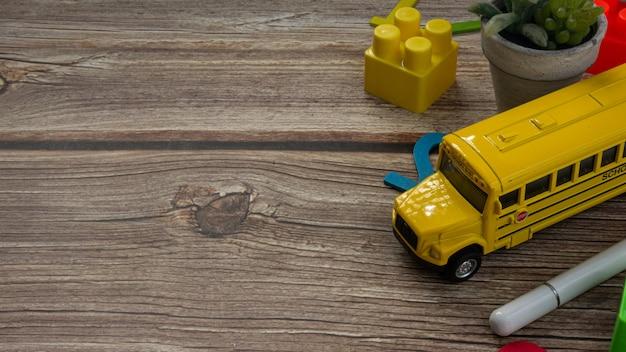 Lo scuolabus sul tavolo di legno per l'istruzione o il concetto di ritorno a scuola