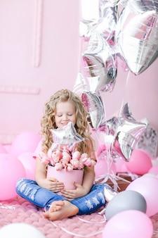 Ragazza dello scolaro che si siede con il canestro rosa con i fiori.