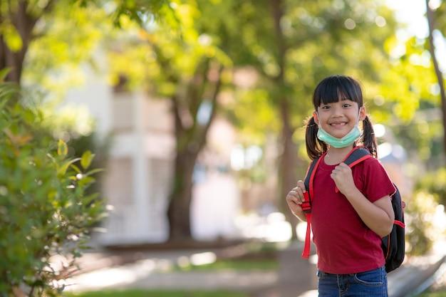 Scolaro che indossa una maschera facciale durante l'epidemia di coronavirus e influenza. sorellastra che torna a scuola dopo la quarantena e il blocco del covid-19. bambini in maschera per la prevenzione del coronavirus.soft focus