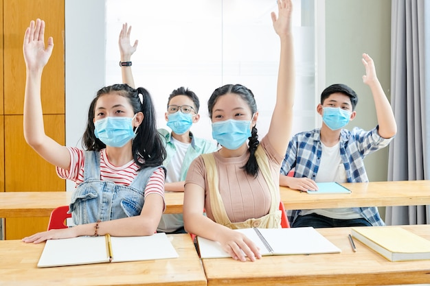 Bambini in età scolare in mascherine mediche che alzano le braccia per rispondere alla domanda dell'insegnante