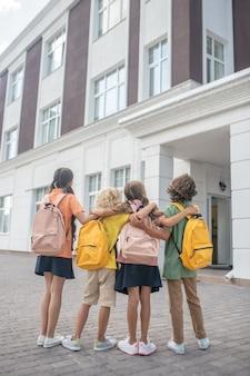 A scuola. bambini in piedi nel cortile della scuola e guardando l'edificio scolastico