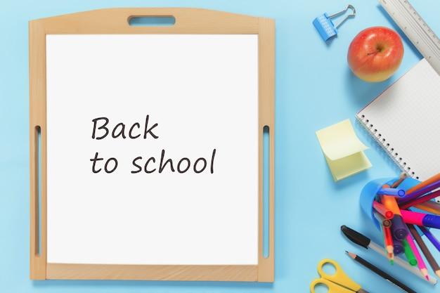 Il concetto di scuola piatto giaceva su una superficie blu con vari accessori per la scuola, penne, matita, blocco note, clip, mela, righello, forbici, testo di ritorno a scuola su lavagna bianca, adesivo di carta su superficie blu