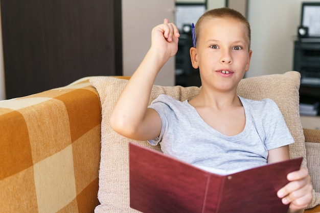 Il ragazzo dei giorni di scuola risolve i compiti sul divano con un quaderno in mano scrive le risposte con una penna ...