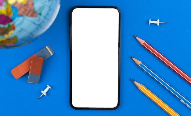 Istruzione scolastica e apprendimento del concetto di mockup del telefono cellulare, schermo bianco vuoto, tavolo con matite, spilla e gomma, foto di sfondo blu