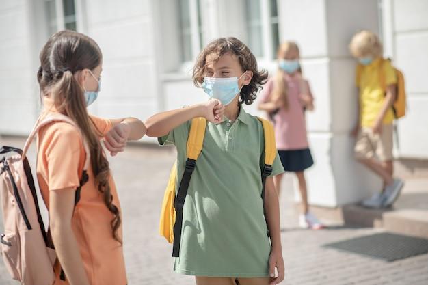 A scuola. amici in maschere protettive nel cortile della scuola si salutano