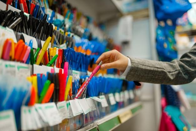 Ragazza della scuola che sceglie una penna sullo scaffale in cartoleria