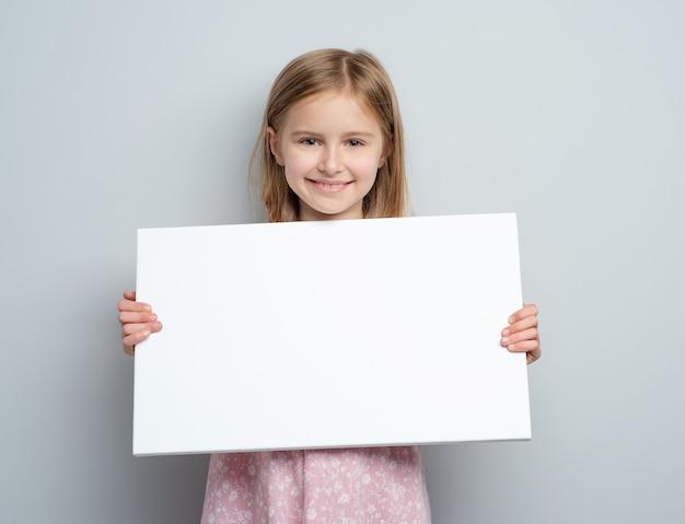 Ragazza della scuola che tiene manifesto bianco in bianco