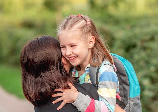 Ragazza della scuola che abbraccia la madre dopo le lezioni nel parco soleggiato