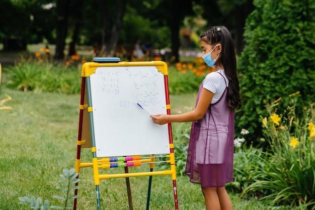 Una ragazza della scuola con una maschera si alza e scrive lezioni sulla lavagna. ritorno a scuola, apprendimento durante la pandemia.