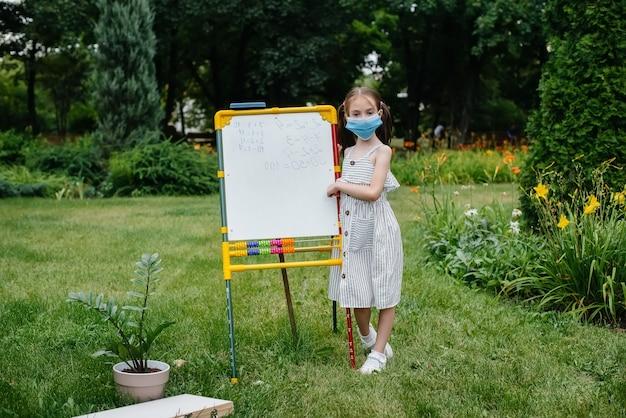 Una studentessa con una maschera si alza e scrive lezioni sulla lavagna