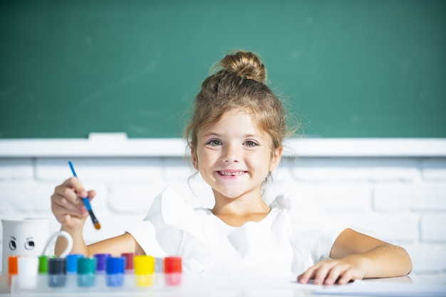 Allievo della ragazza della scuola che disegna un'immagine. simpatico bambino in età prescolare che disegna a scuola.