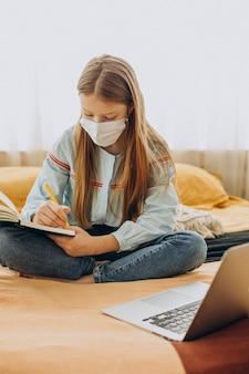 Ragazza della scuola che studia a casa che indossa la maschera, apprendimento a distanza