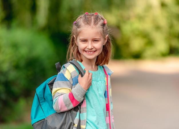 Ragazza della scuola che cammina attraverso il parco dopo la scuola