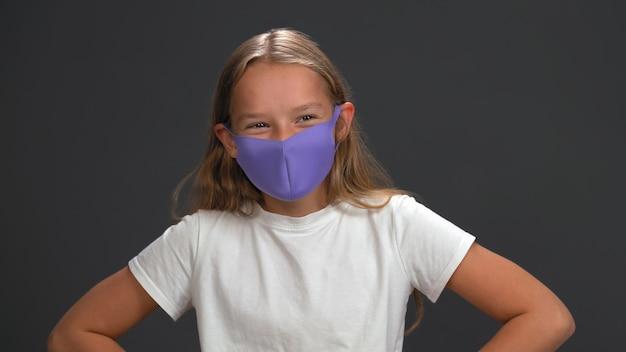 Ragazza della scuola che indossa la maschera facciale riutilizzabile blu che indossa la maglietta bianca che sorride con i suoi occhi