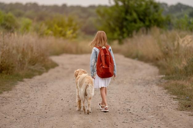 Ragazza della scuola con zaino e cane golden retriever che cammina nel campo. preteen bambino bambino con cagnolino in natura
