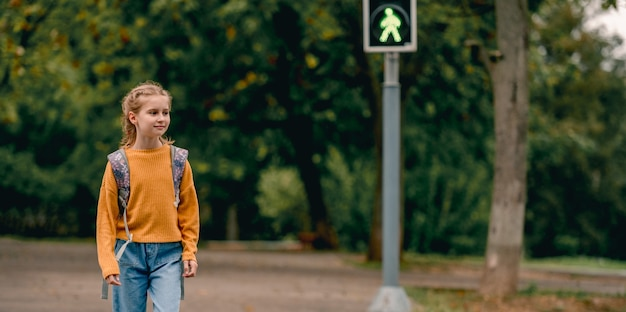 Ragazza della scuola con lo zaino a piedi all'aperto. bambina graziosa dopo le lezioni che torna a casa