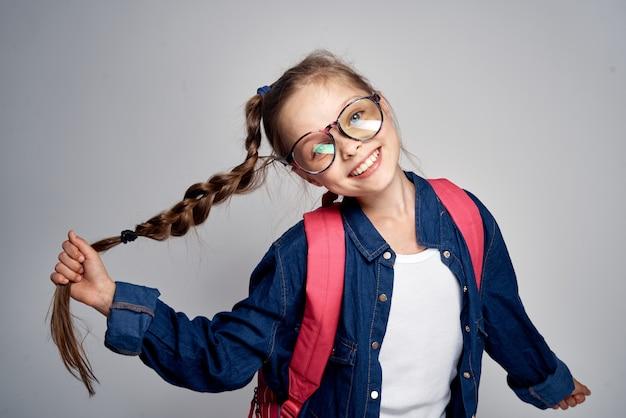 Scuola ragazza con zaino rosa swoosh codino divertente apprendimento sfondo chiaro scuola infanzia