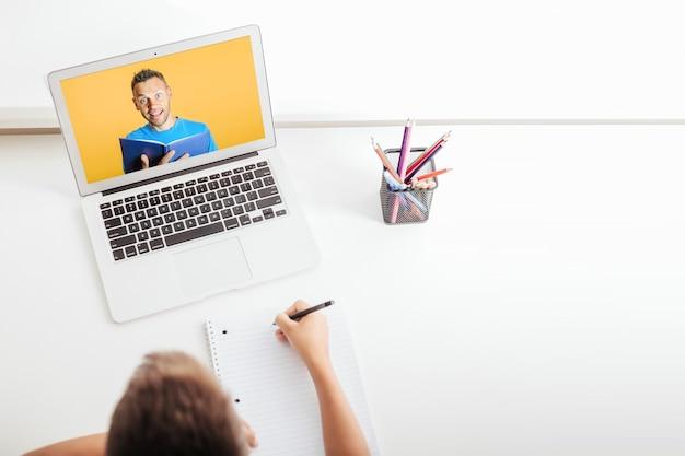 Scuola a casa attraverso l'istruzione domestica online. il bambino è seduto al computer