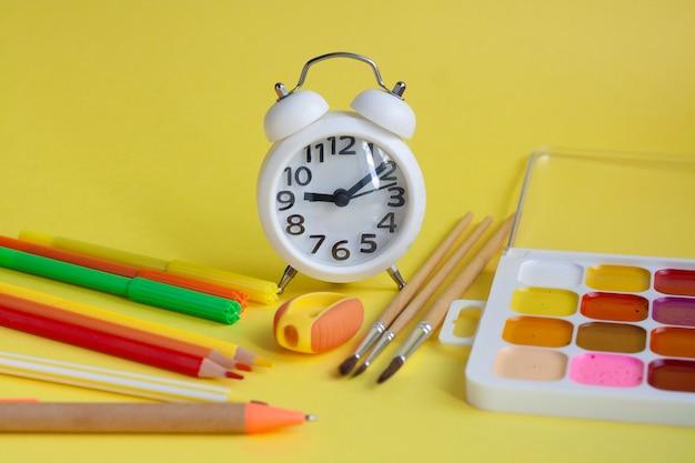 Compiti scolastici, sveglia, matite, pennarelli, taccuino, penna, righello, temperino, acquerelli e pennelli su un tavolo giallo