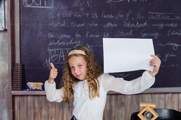 La scuola è un posto felice bambino piccolo felice che tiene carta bianca sullo sfondo della lavagna bambina h...