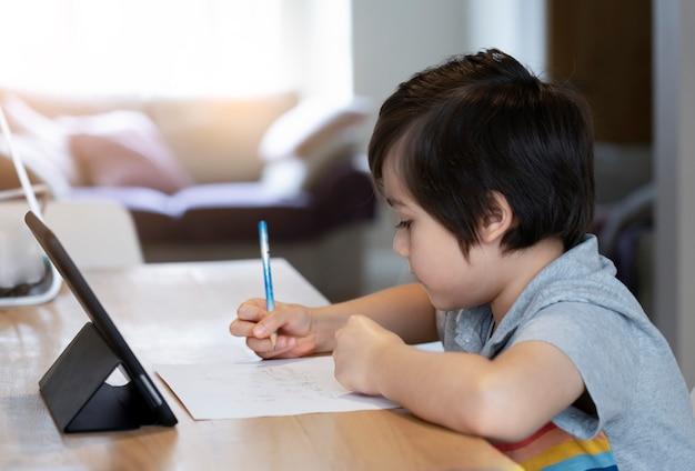 Autoisolamento del bambino della scuola facendo uso della compressa per i suoi compiti, bambino che fa i compiti usando la compressa digitale che cerca informazioni. formazione online a distanza