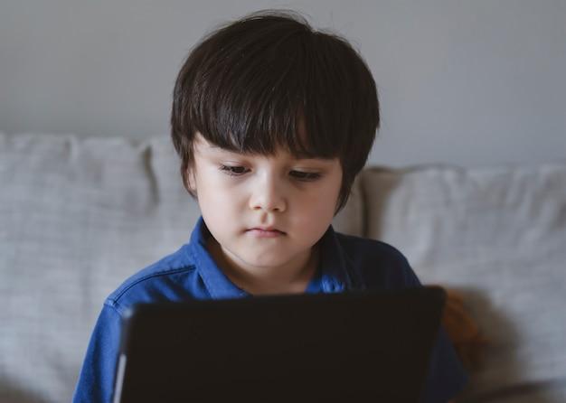 Bambino della scuola che utilizza la tavoletta per i compiti, bambino che guarda la tavoletta digitale con la faccia pensante, ragazzo che guarda i cartoni animati sul touchpad, nuova vita normale con apprendimento online, formazione a distanza