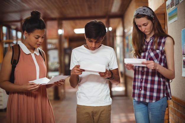 Ragazzi delle scuole che controllano la carta delle domande nel corridoio