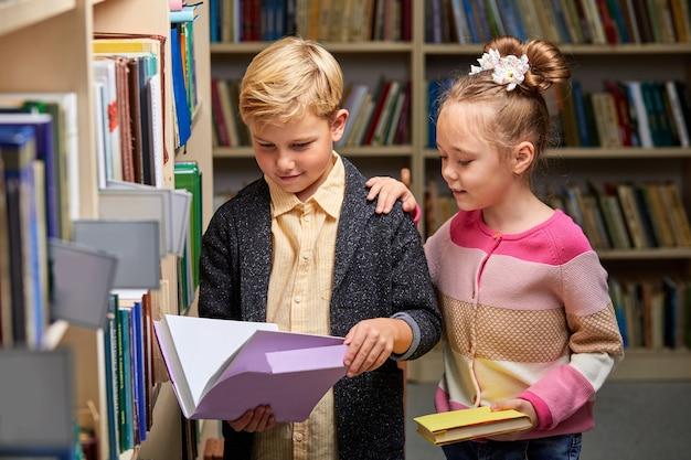 Ragazzi delle scuole che si preparano per la lezione nella biblioteca della scuola, leggono insieme libri di testo e discutono, concetto di educazione