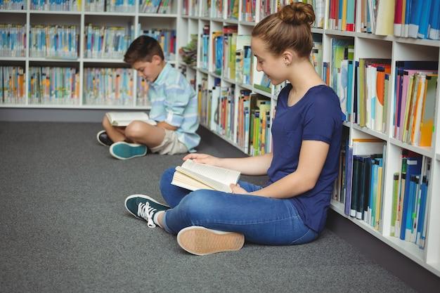 Scuola bambini a leggere libri in biblioteca a scuola