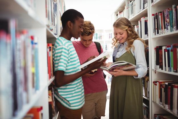 Ragazzi delle scuole che leggono libri in biblioteca a scuola