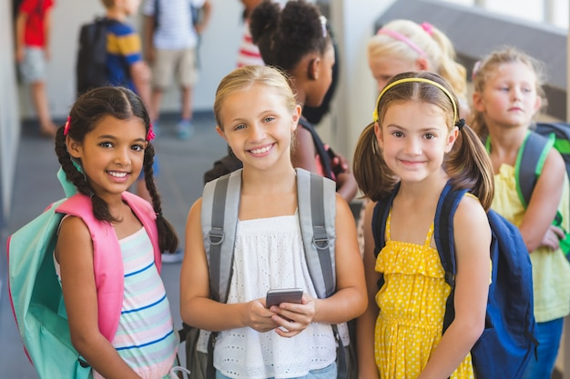 Bambini della scuola che stanno in corridoio con il telefono cellulare